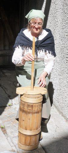 Baeuerin bei der Butterherstellung in Zermatt vor 100 Jahren beim Dorfrundgang