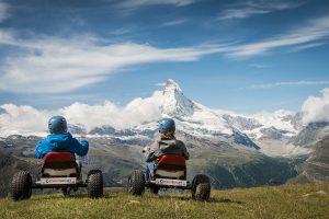 Bergkulisse und Kinder auf Mountaincart