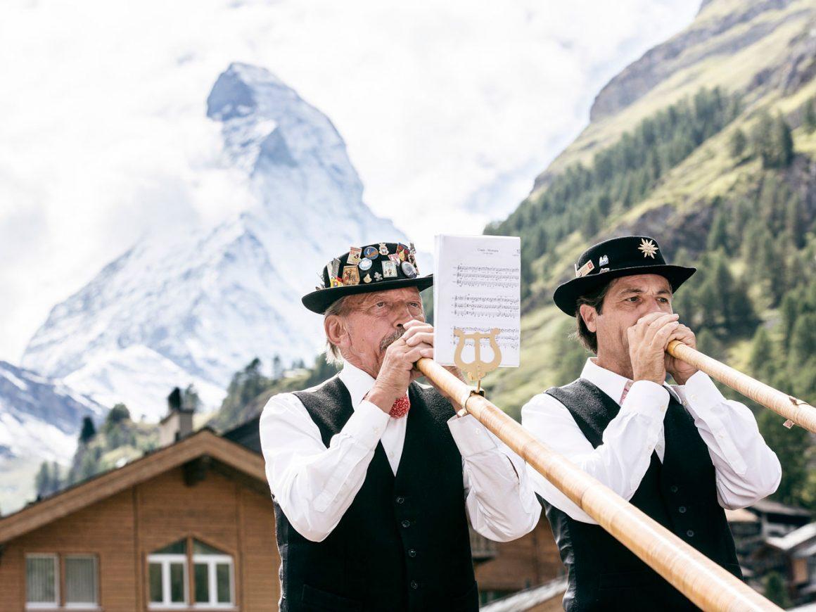 Zwei Männer mit riesen Trompeten vor dem Matterhorn